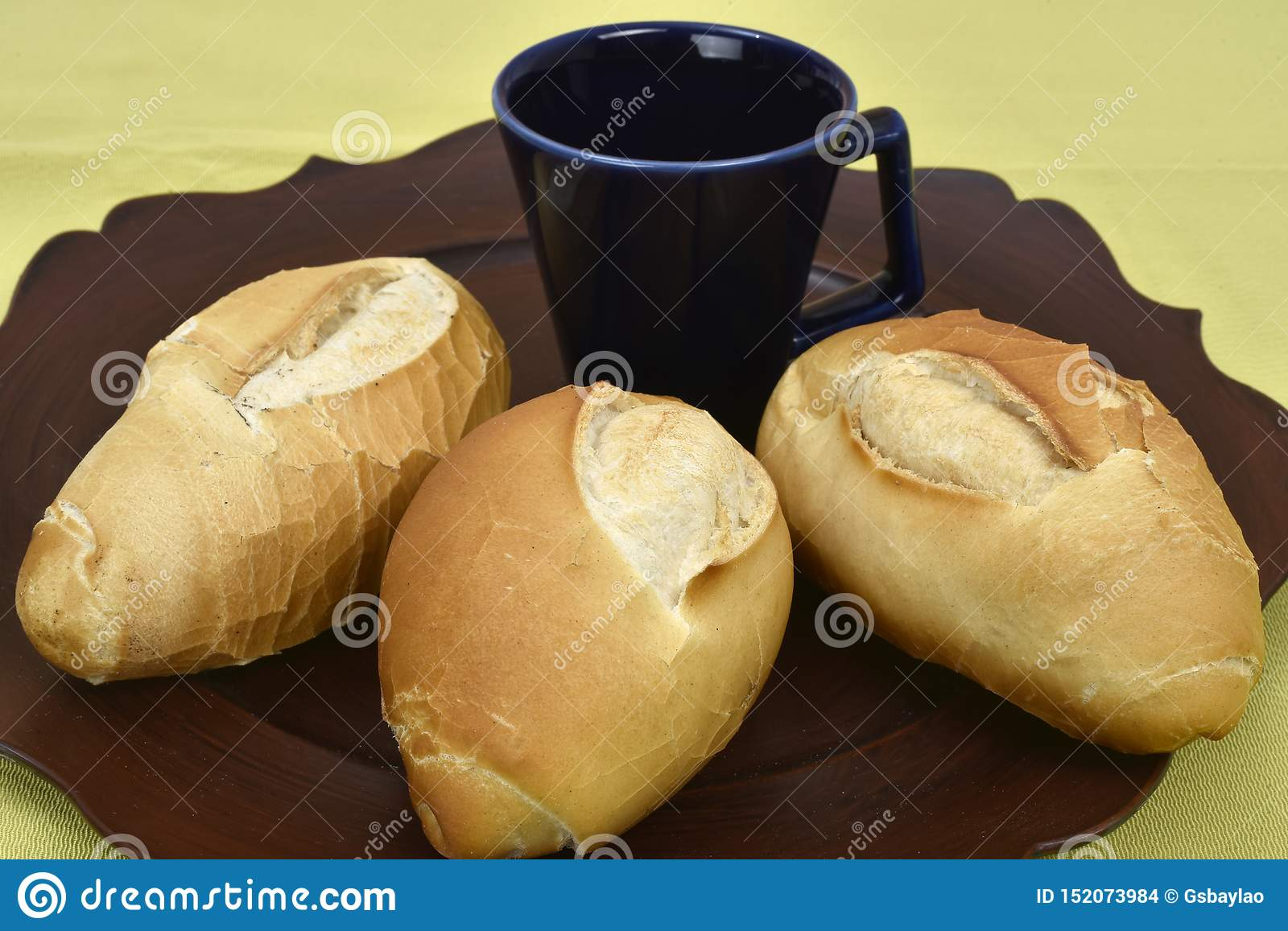 French bread on the plate with black cup in the background