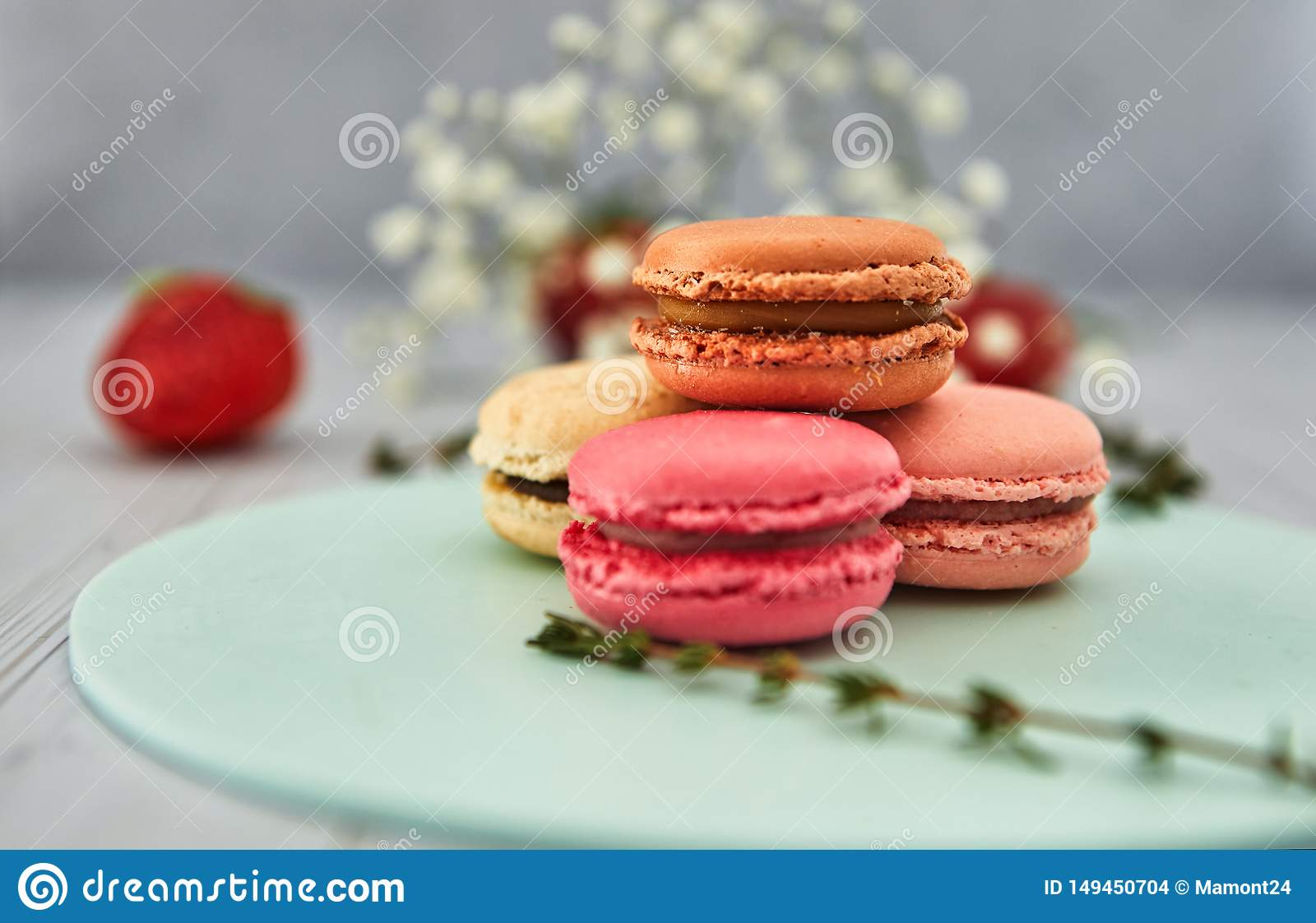 French colorful macaroons. Colorful pastel macaroons on a light background with fresh strawberries