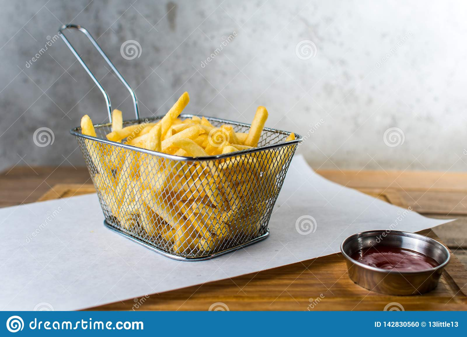French fries in iron grid and sauce