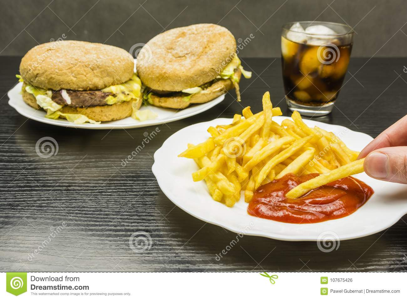 French fries and ketchup on a plate and a burger and cola with i