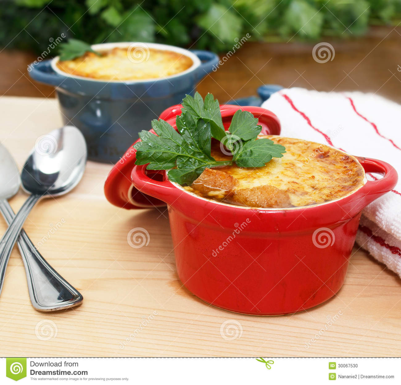 French Onion Soup Gratin in red and blue pots on table top.