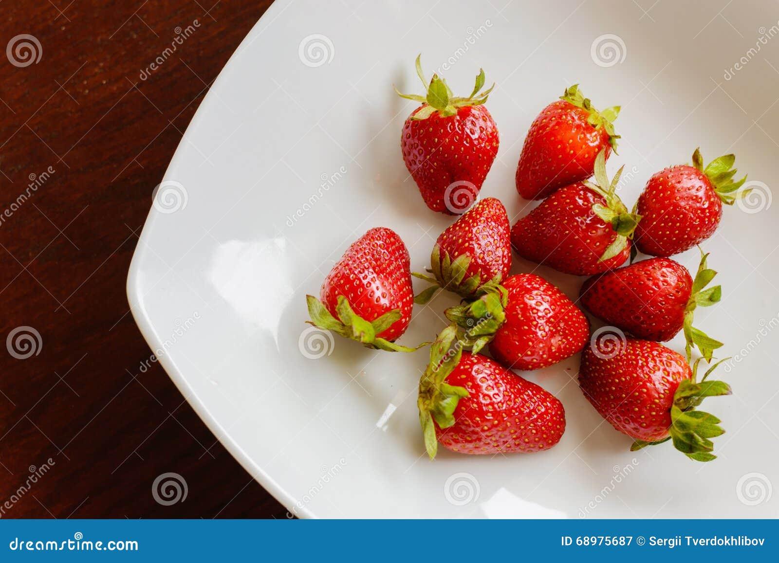 Fresas rojas maduras en la tabla de madera