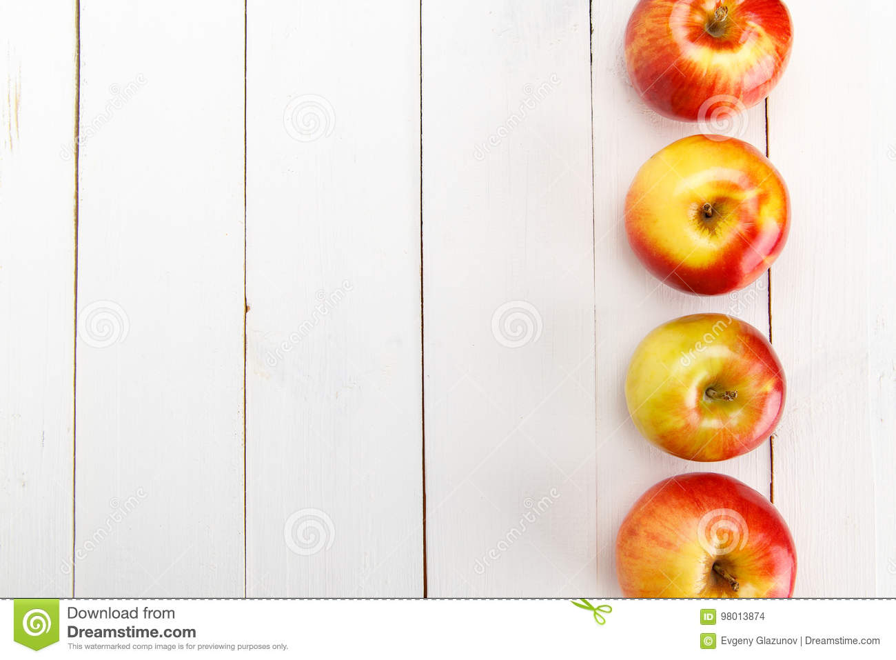 Fresh apples on a white wooden table