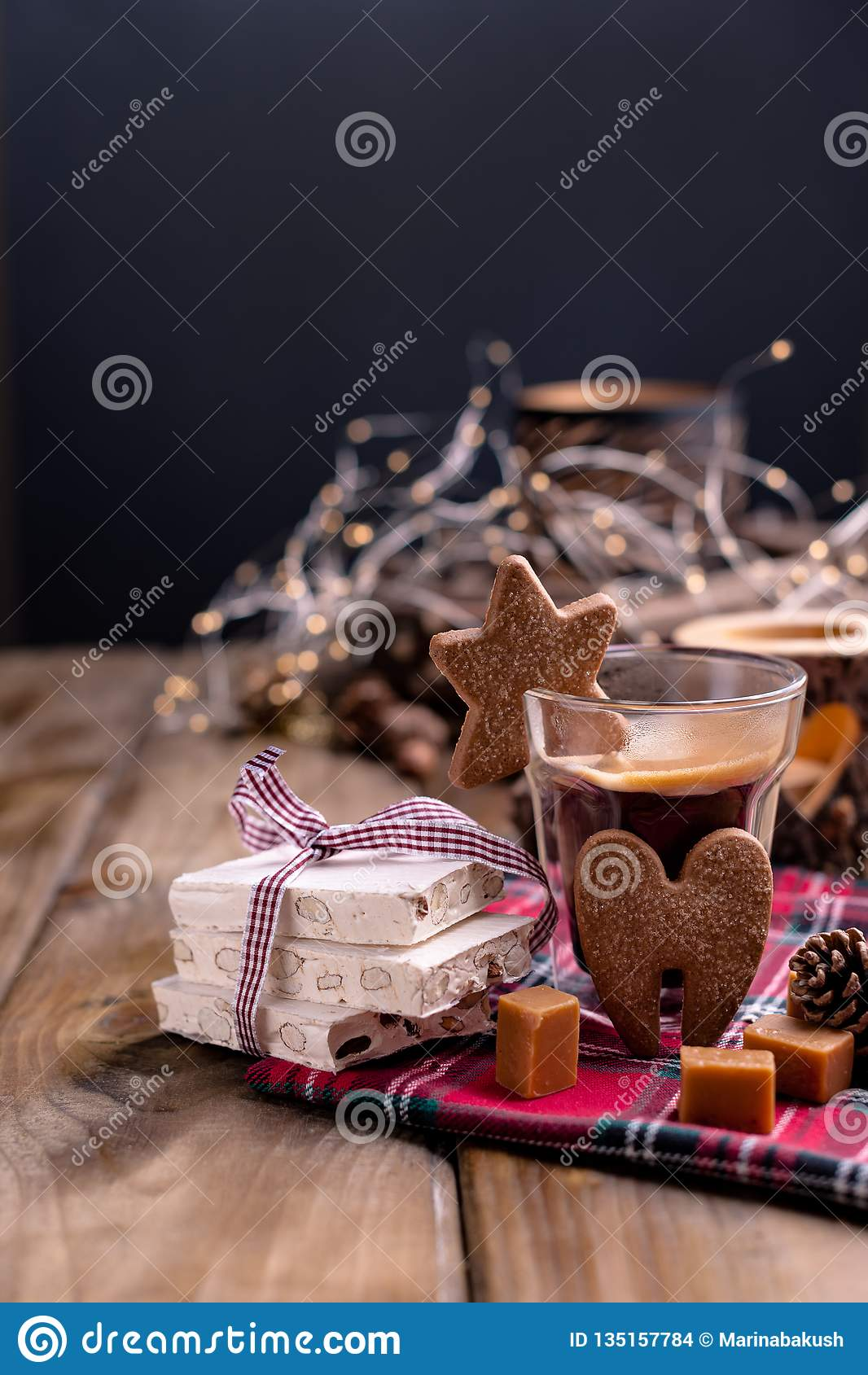Fresh aromatic coffee and Italian Christmas sweets. Nougat with almonds, karemelnye sweets, ginger cookies and hot drink. Candles