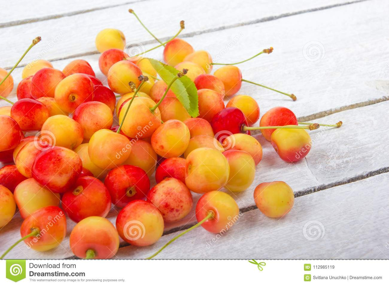Cherry in a bowl. Fresh yellow cherry. Cherry on a white wooden background. The concept of a healthy diet. Berries