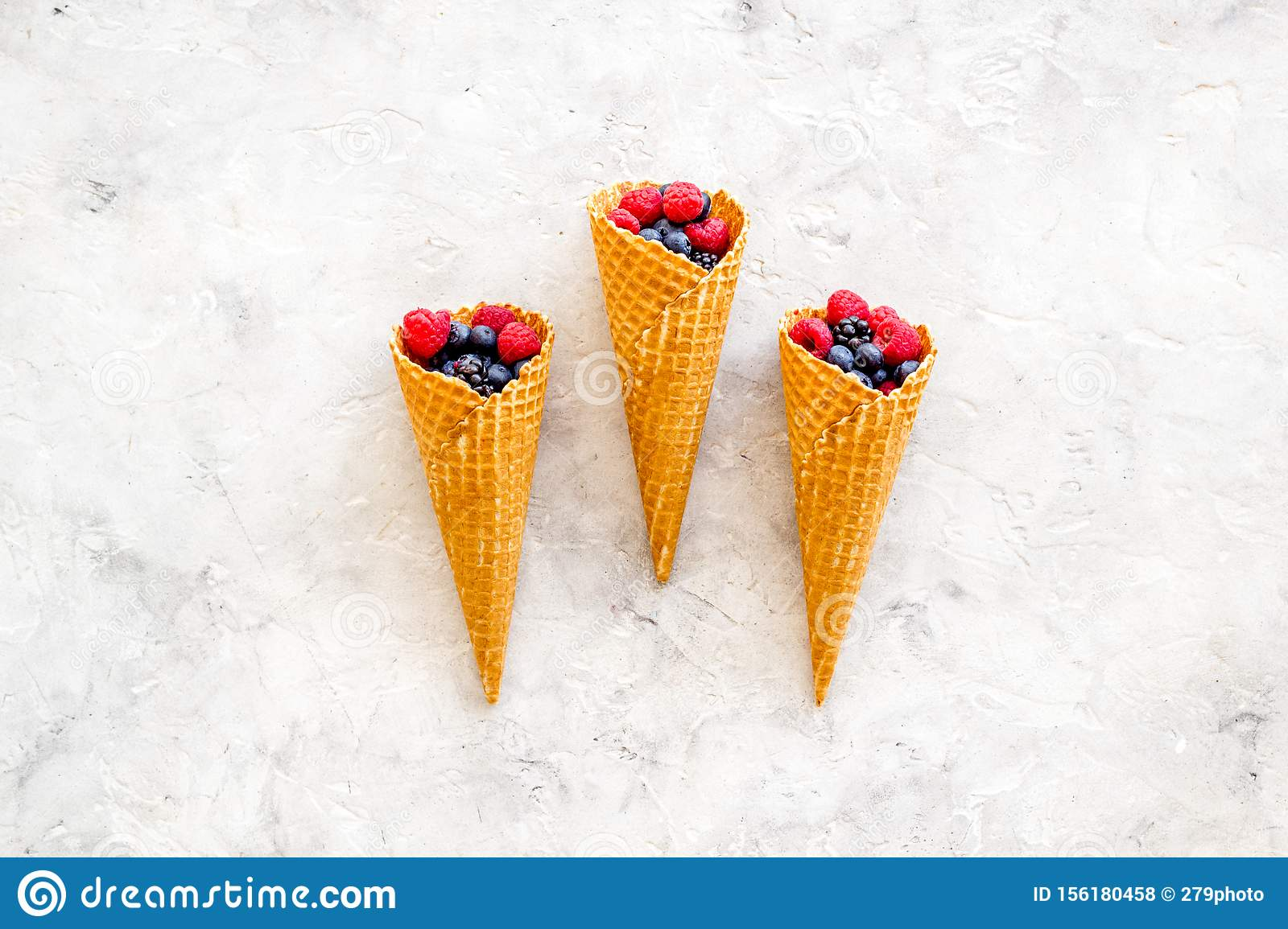 Fresh berries in waffle cones on light stone background top view