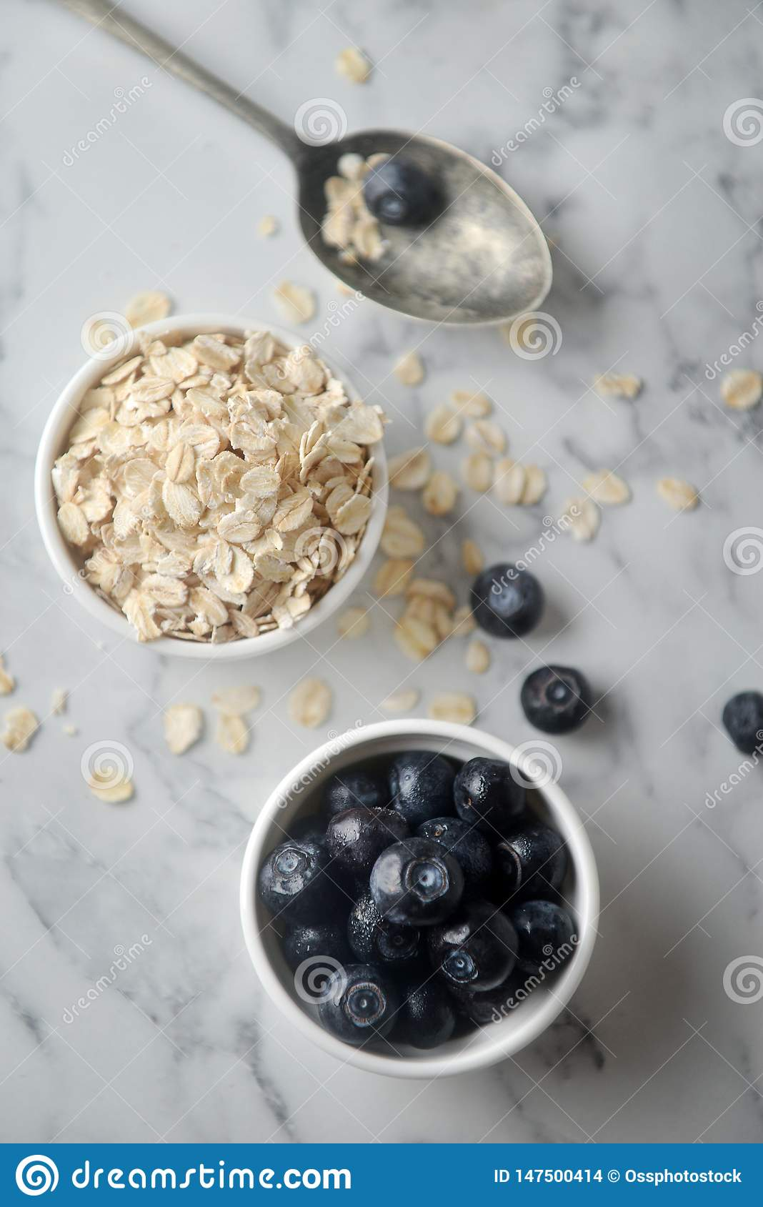 A fresh blueberries and Organic rolled oats in bowl, on marble background. Concept of cooking ingredients, decorate bakery,