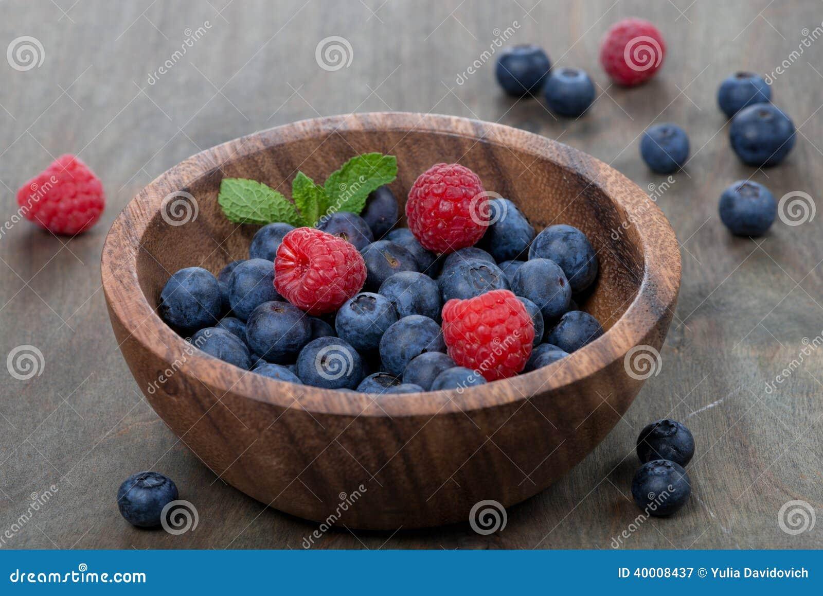 Fresh blueberries and raspberries in wooden bowl