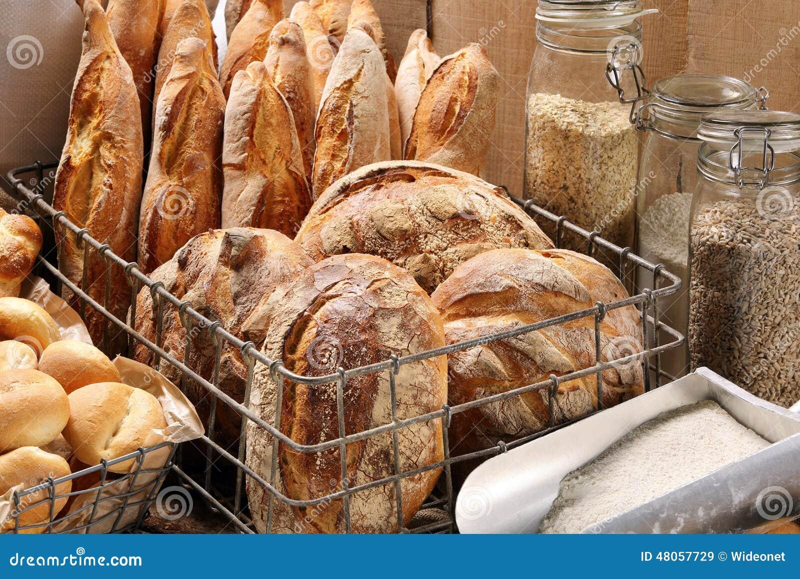 Fresh bread in metal basket in bakery on wooden background