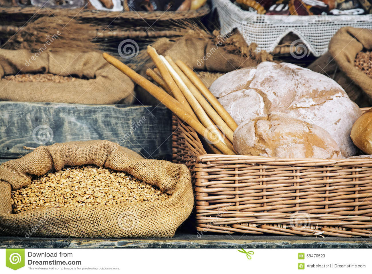 Fresh bread with pastry in the wicker basket and grain in the ba