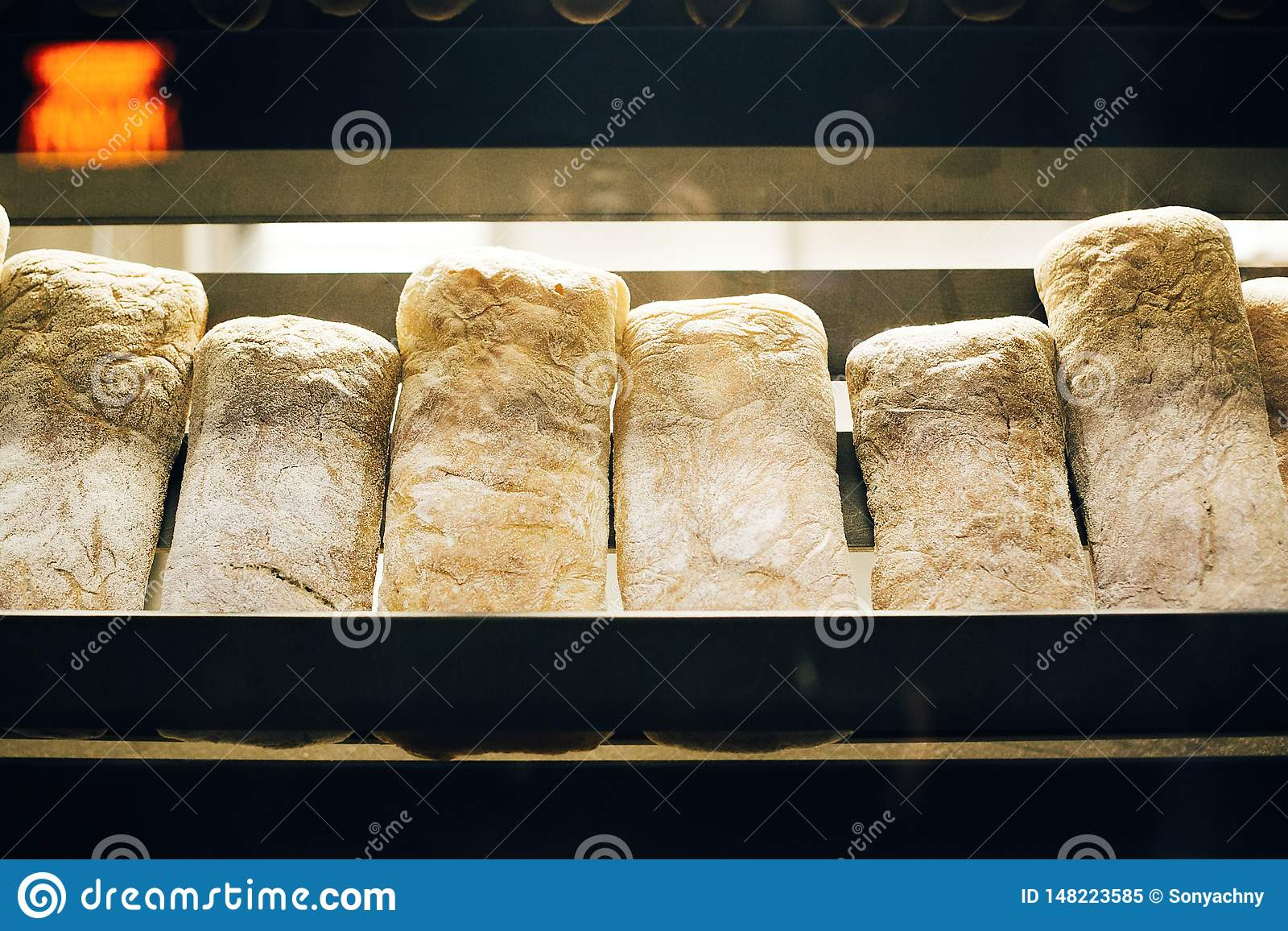 Fresh bread on shelves stand of a shop or bakery. Freshly baked bread loaves at window of store front. Organic pastry. Space for