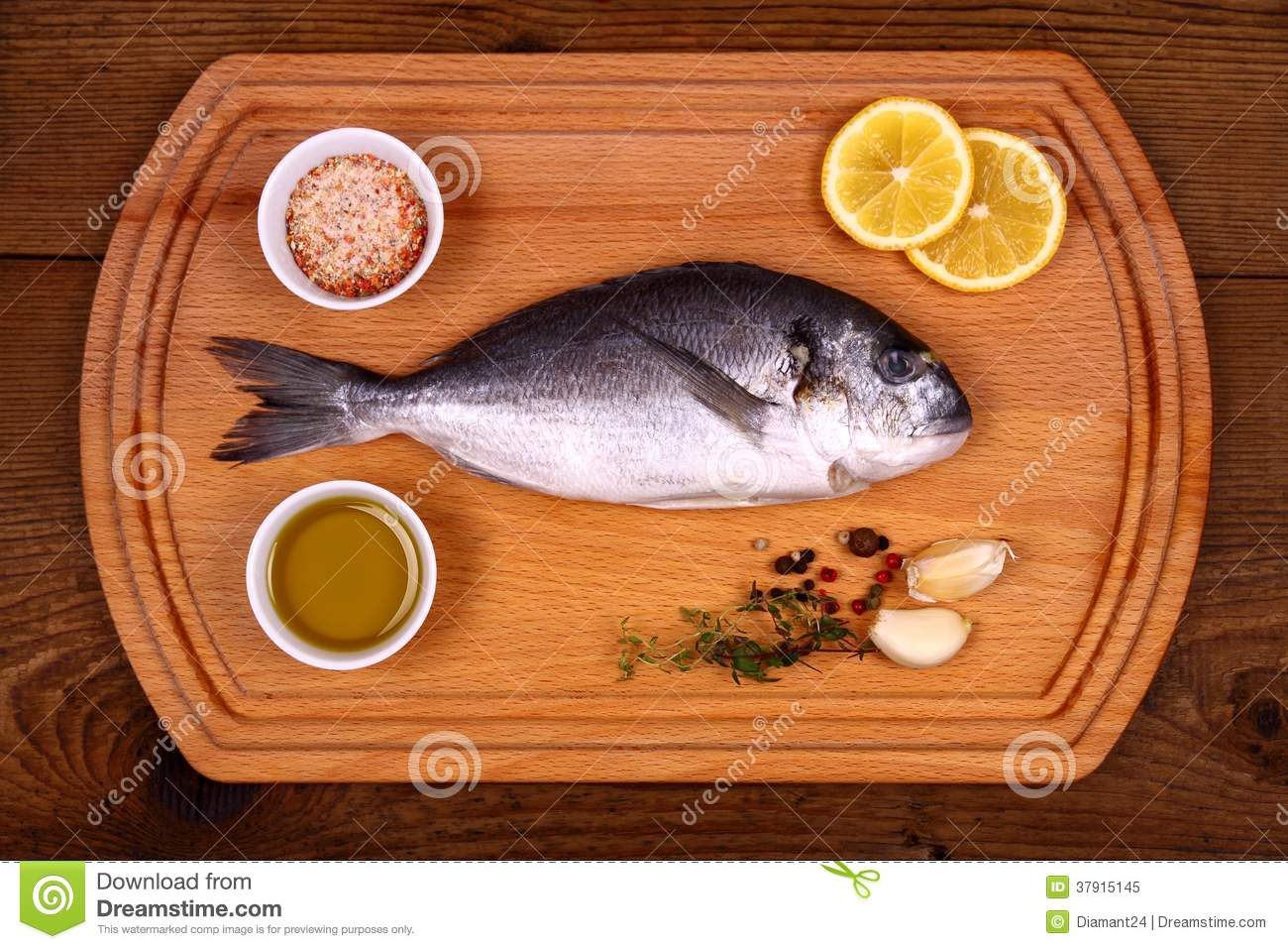 Fresh bream fish on cutting board with ingredients stock for Fish cutting board