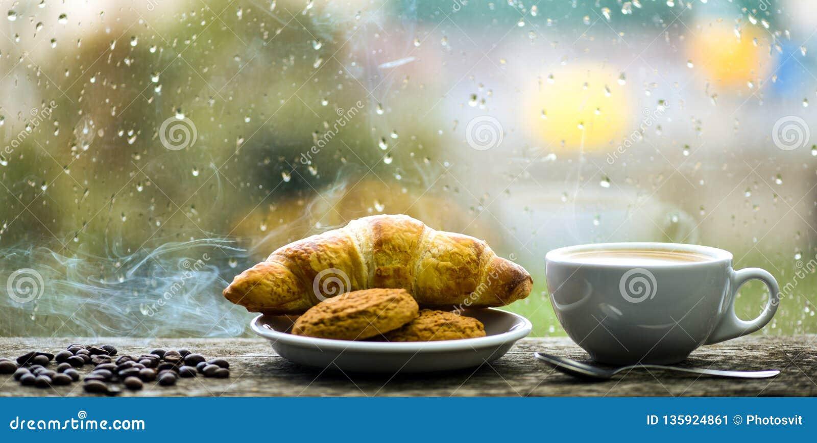 Fresh brewed coffee in white cup or mug on windowsill. Coffee drink with croissant dessert. Enjoying coffee on rainy day