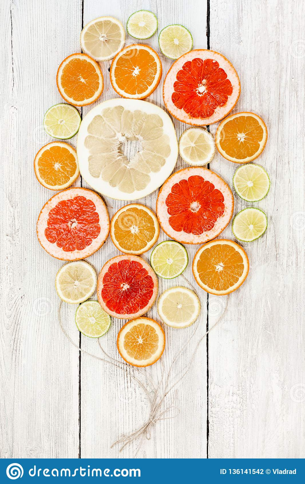 Fresh bright juicy citrus sliced and collected together with craft ropes as balloons. In white wood background. lemon