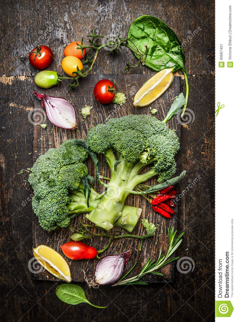 Fresh broccoli and vegetables ingredients and seasoning for tasty vegetarian cooking on rustic wooden background, top view