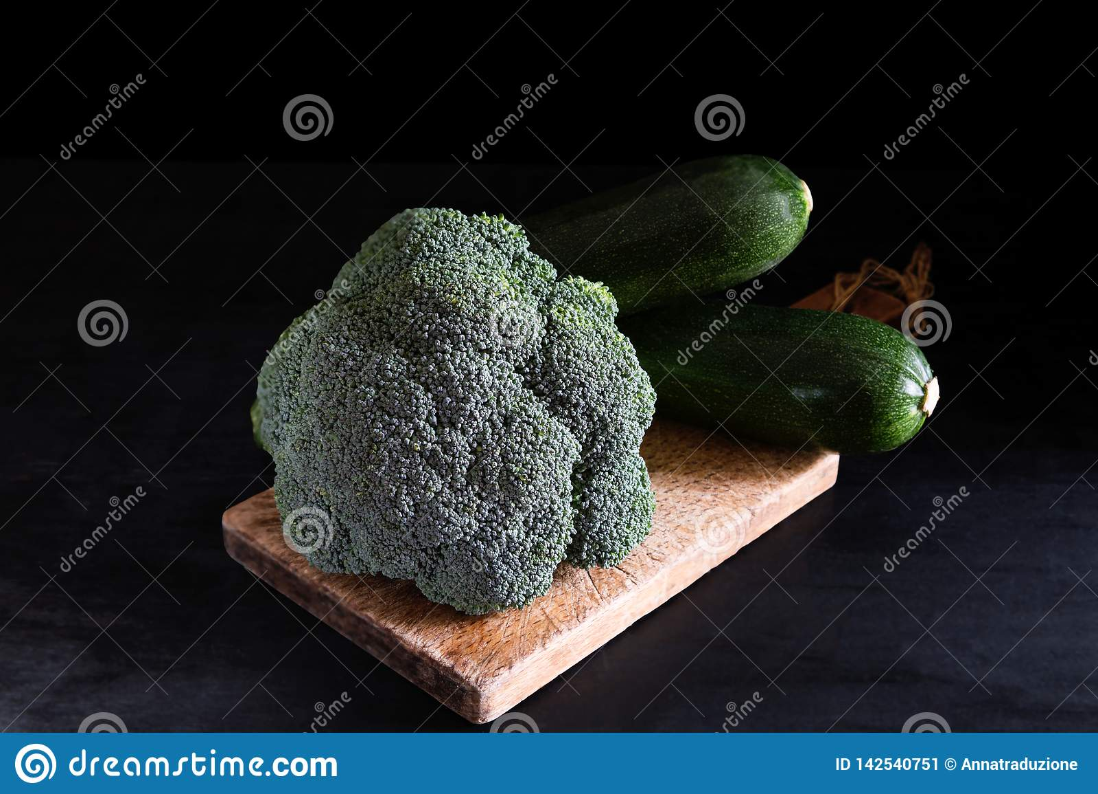 Fresh broccoli and zucchini on a cutting board on a black background, rustic style, dark key. Healthy food