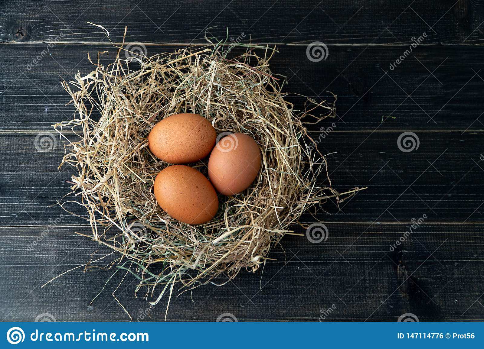Fresh brown chicken eggs in hay nest on black wooden background. Concept of organic eggs, free space for text or other elements