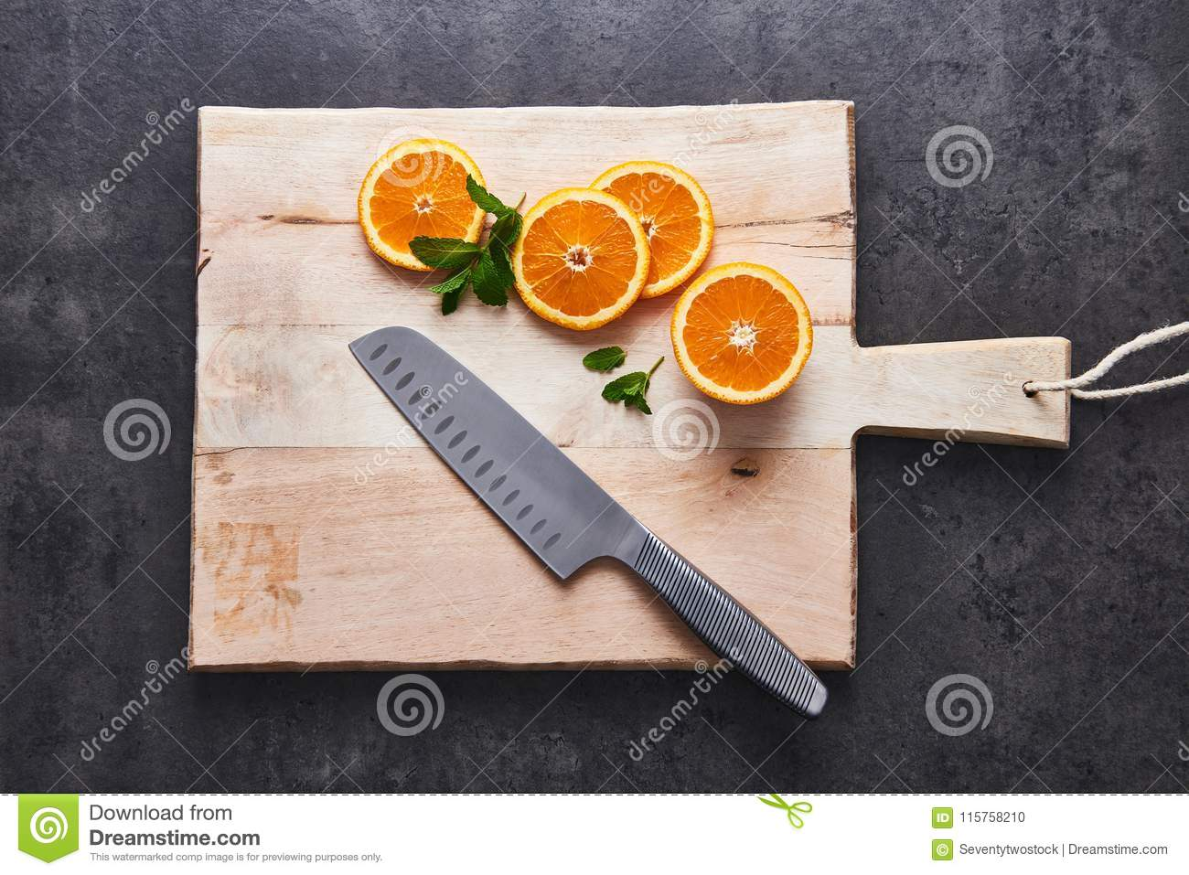 Fresh citrus fruits, half cut orange slices on cutting board with knife on dark stone background, flat lay