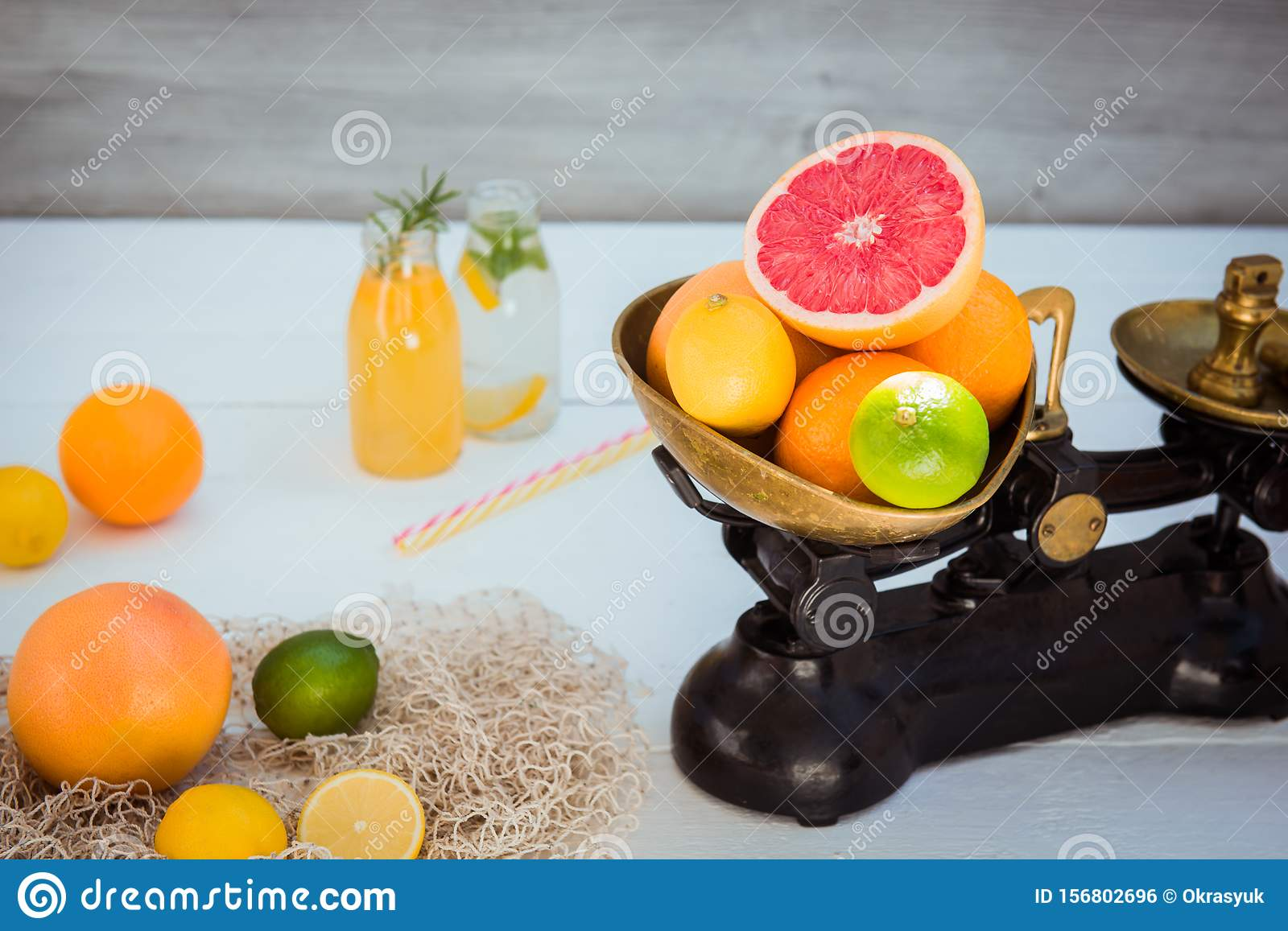 Fresh citrus fruits in vintage scale and several oranges, lemons, grapefruit, lime and homemade drinks on the white wooden table