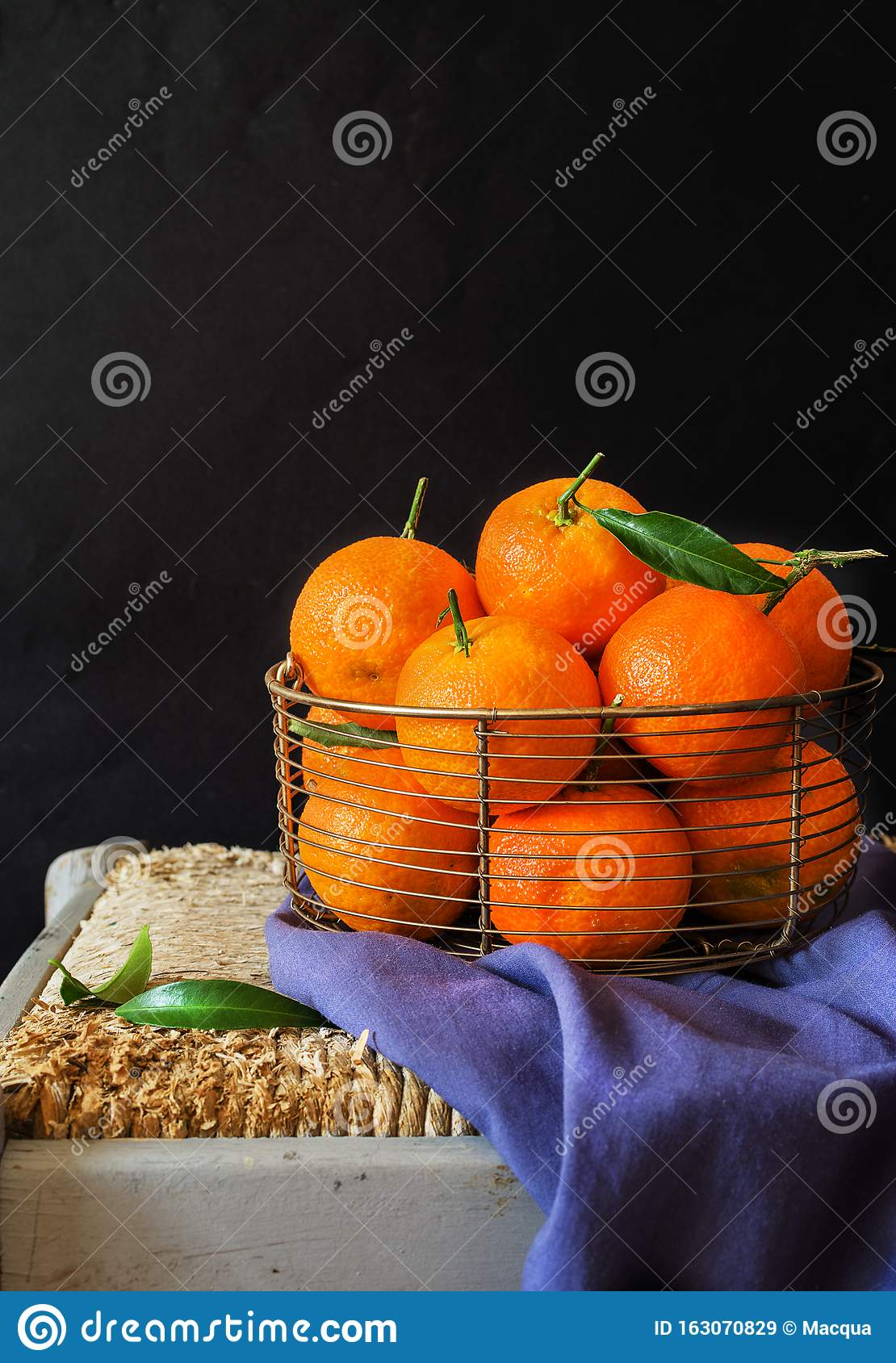 Fresh clementines, in a metellic basket on black background
