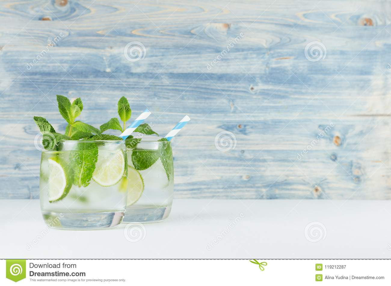 Fresh cold summer beverage with lime, leaf mint, straw, ice cubes on light blue wooden background.
