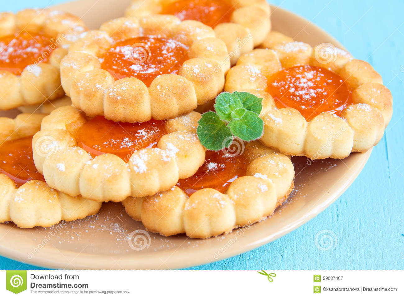 fresh cookies with fruit orange jelly and mint on plate over rustic