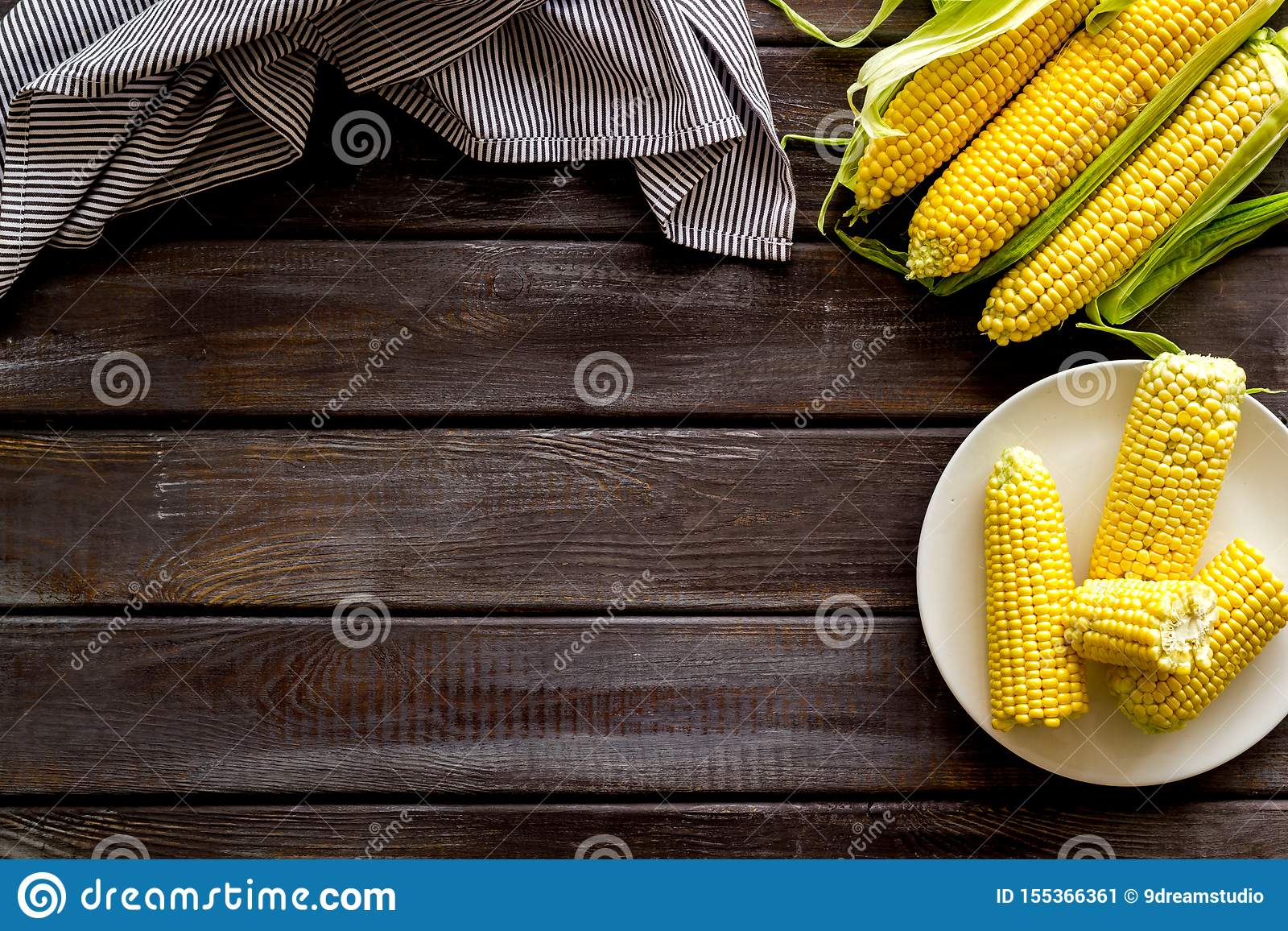Fresh corn on plate as farm food on wooden background top view space for text