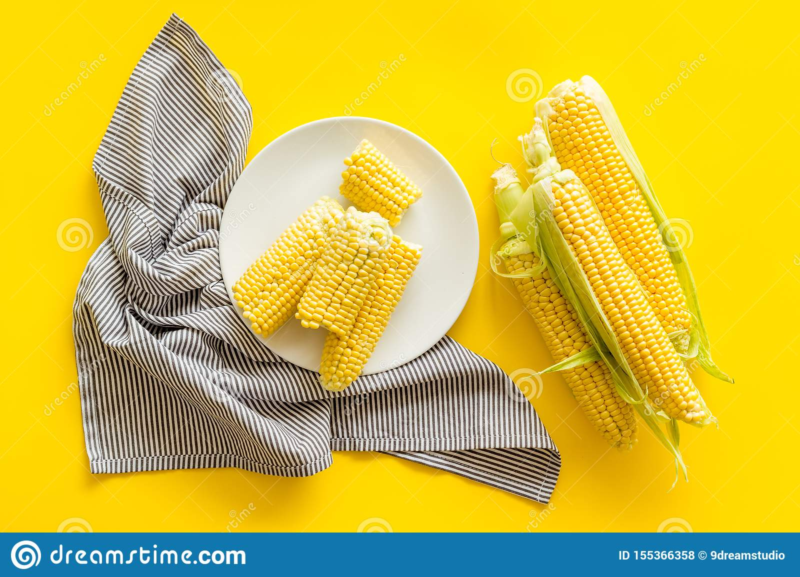 Fresh corn on plate as farm food on yellow background top view