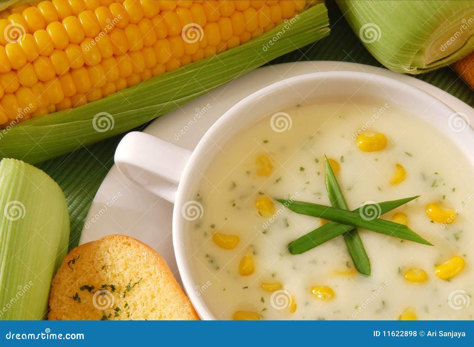 Fresh corn soup with bread and fresh corn on studio setting.