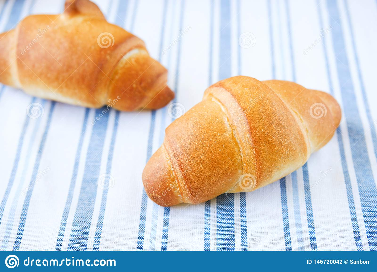 Fresh croissants on a striped linen towel. Freshly baked bakery products close-up. The concept of organic, farm food. The view