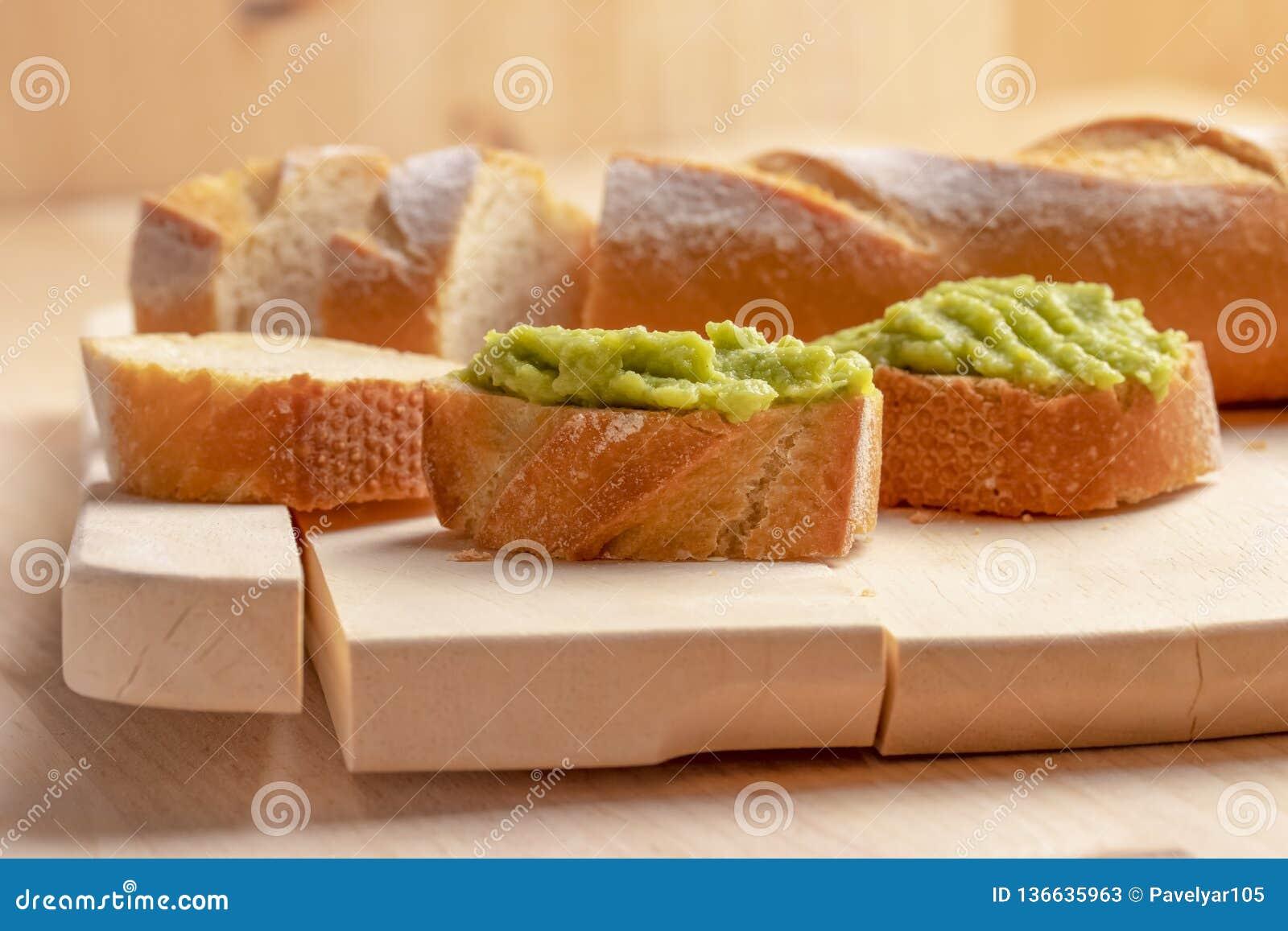 Fresh crunchy avocado cream sandwiches on sliced board