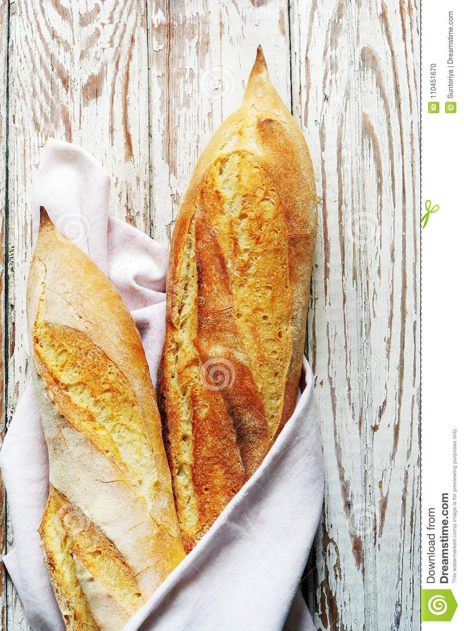 Freshly French baguette with ruddy crispy crust on a light background