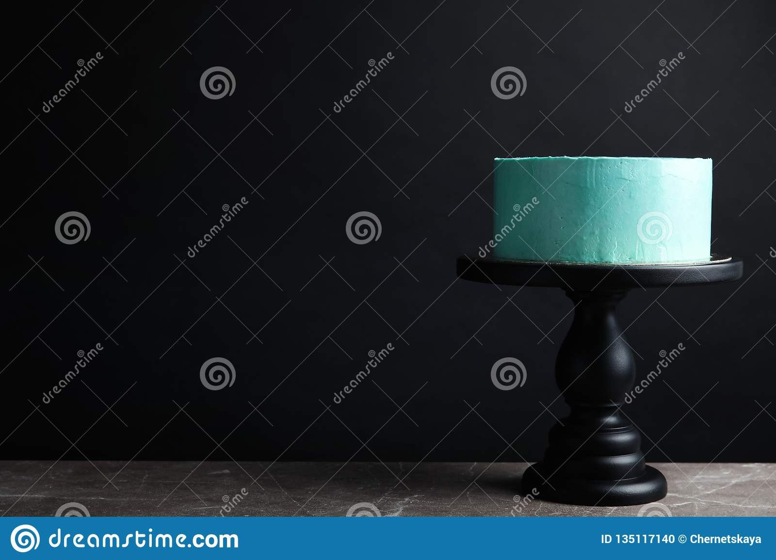 Fresh delicious birthday cake on stand against black background.