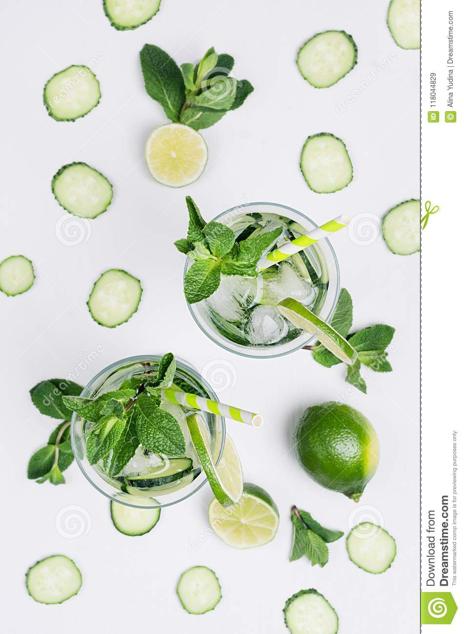 Fresh detox spring cocktail with mint, lime, ice, cucumber, straw on soft white wooden board as fun summer holiday background.