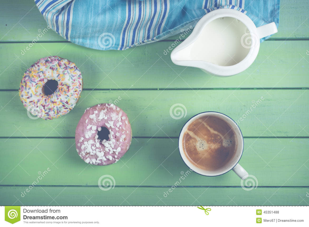 Fresh donuts and coffee on table