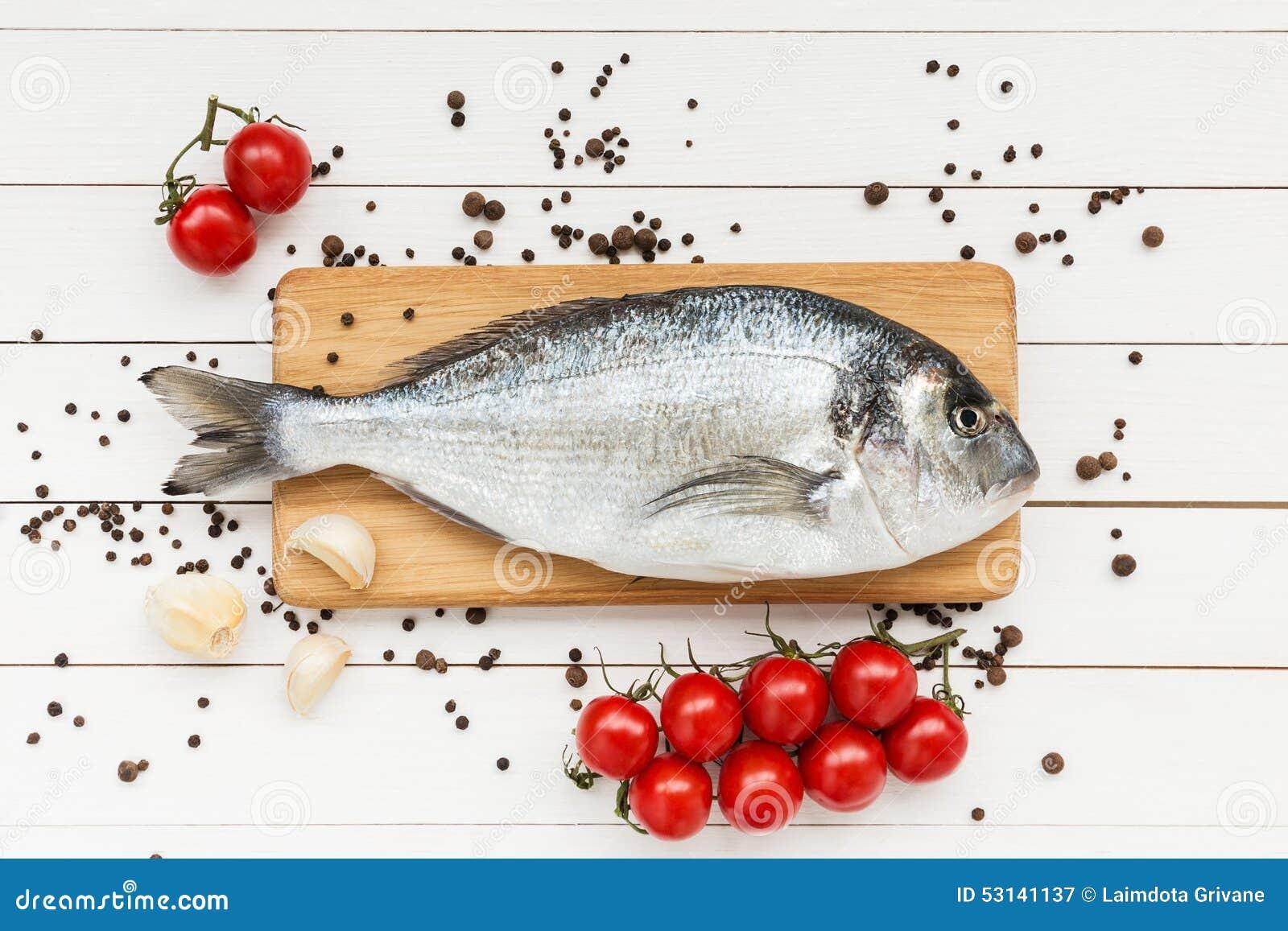 Fresh dorado fish on wooden cutting board with cherry for Fish cutting board