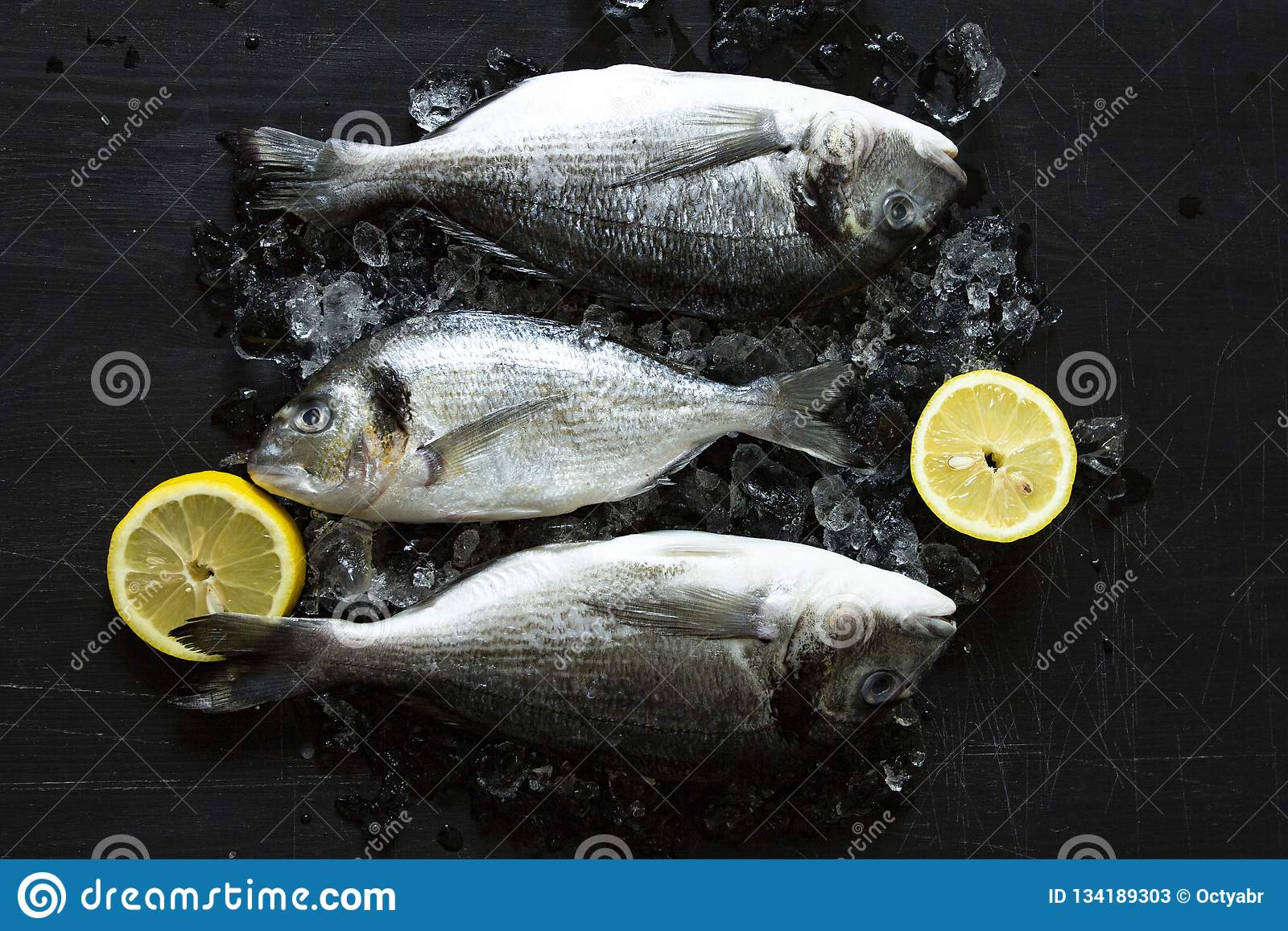 Fresh dorado or sea bream fish with lemon and ice wooden board over black background