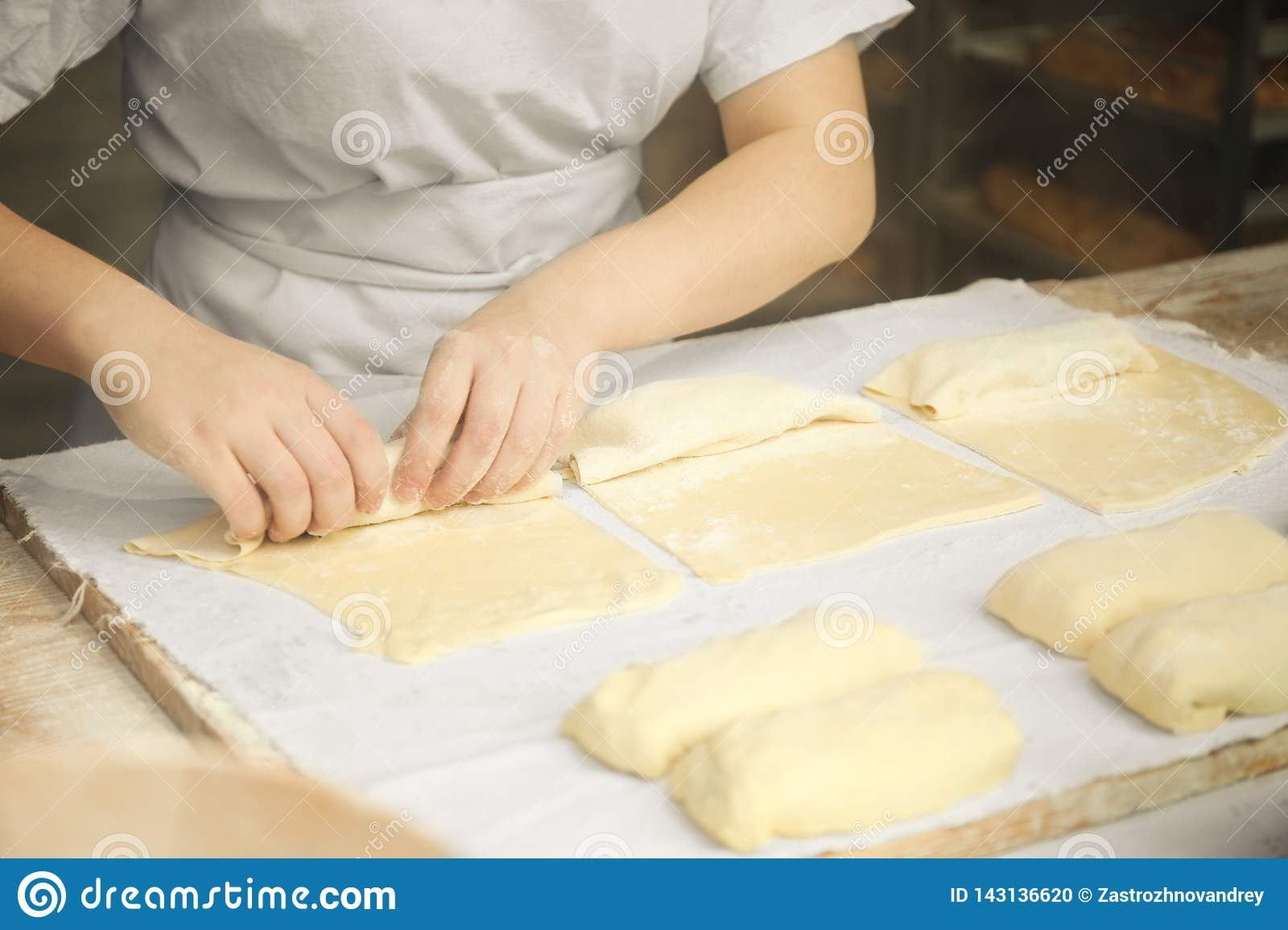 Fresh dough and flour, hands of the cook knead pizza or pie