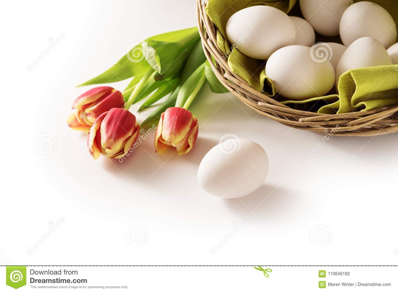 Fresh easter eggs in a basket and red tulips as a holiday corner