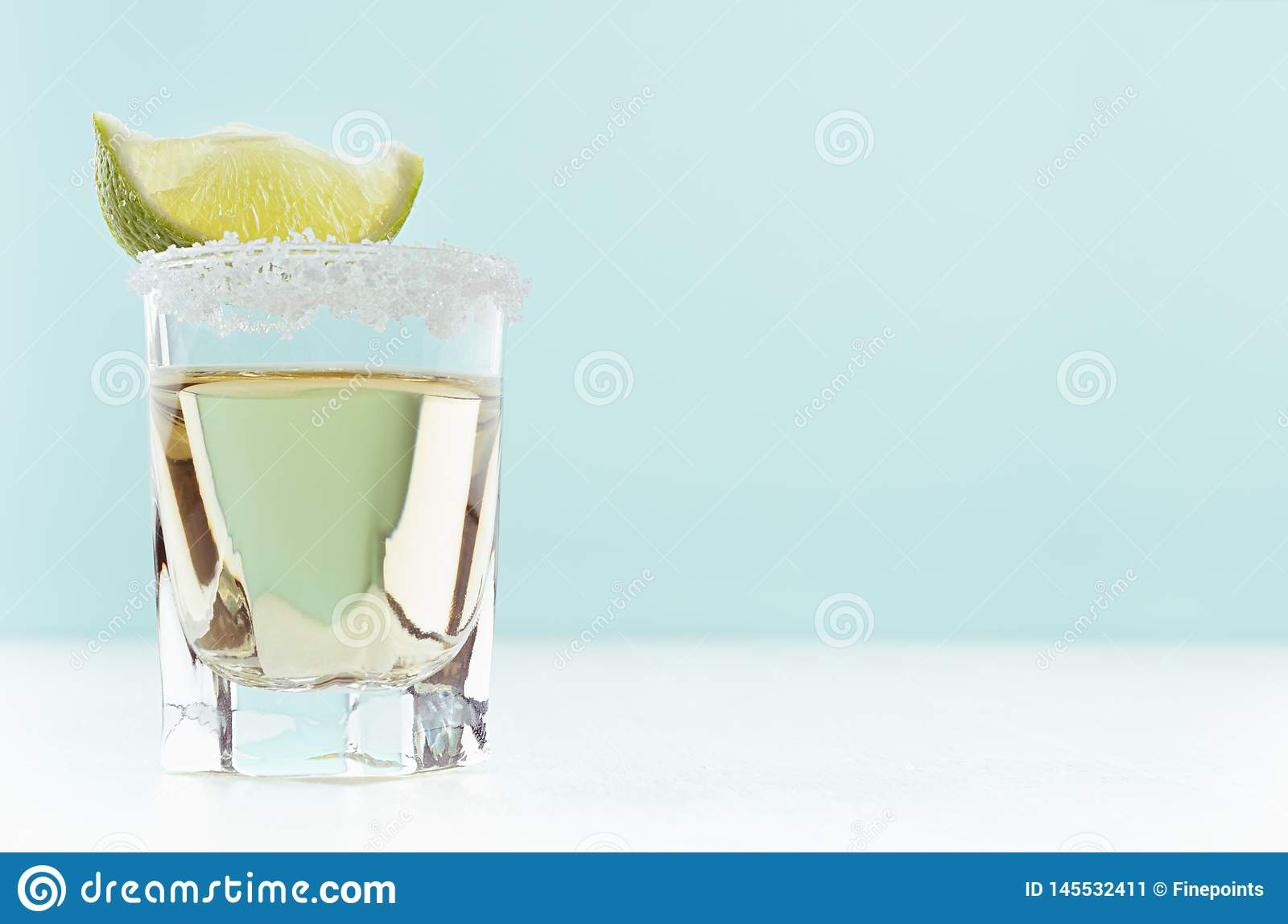 Fresh exquisite shot drink of gold tequila with salt rim and juicy piece green lime closeup in soft light mint color bar interior.