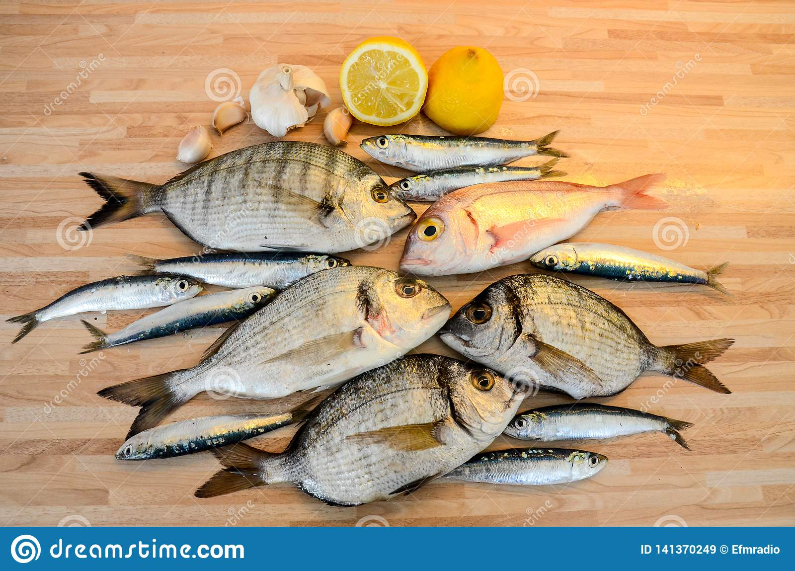 Fresh fish with lemon ready for cooking. Preparing delicious and tasty seafood meal. Uncooked Gilt-head sea bream, Sardines, Commo