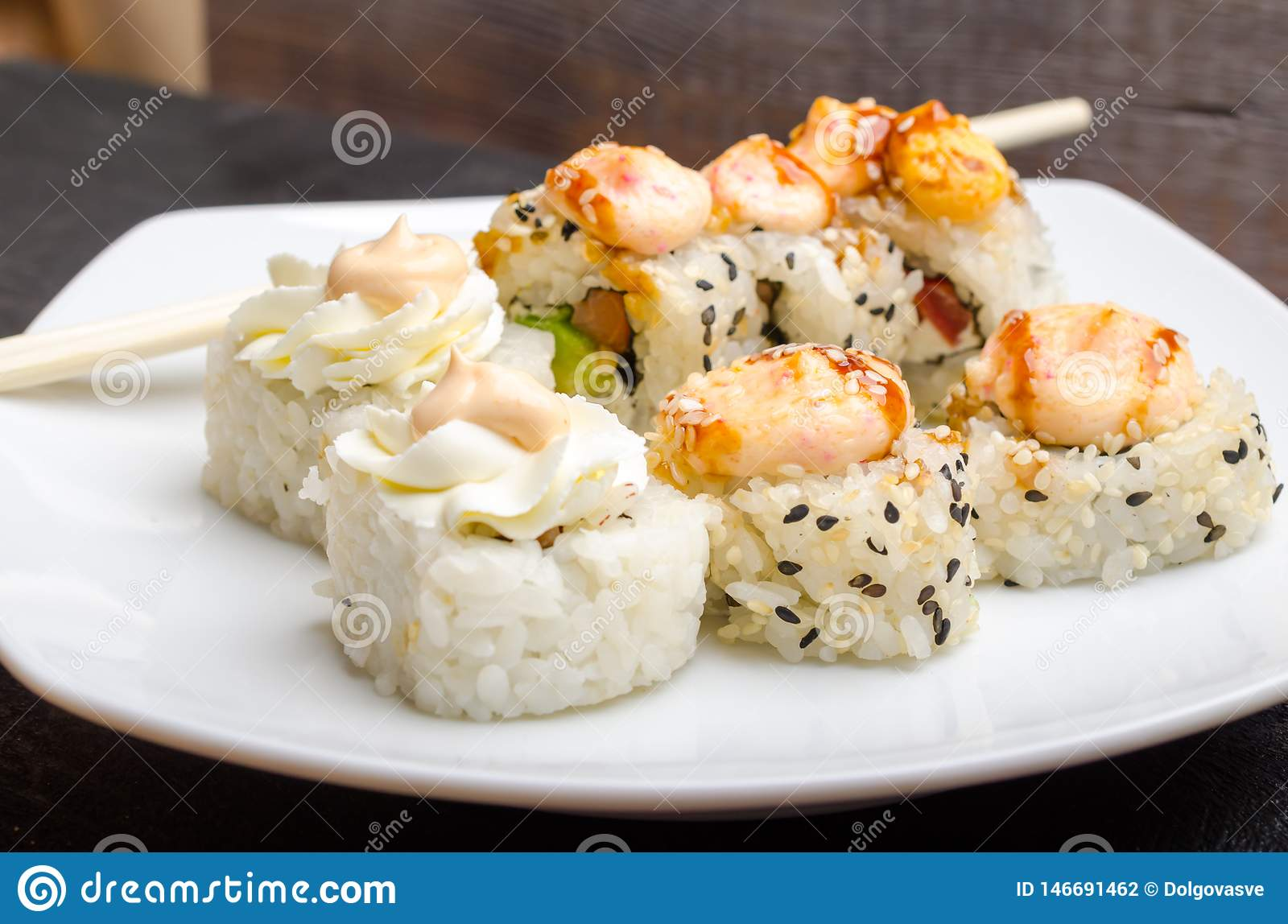 A set of cut Japanese sushi rolls on a white plate closeup