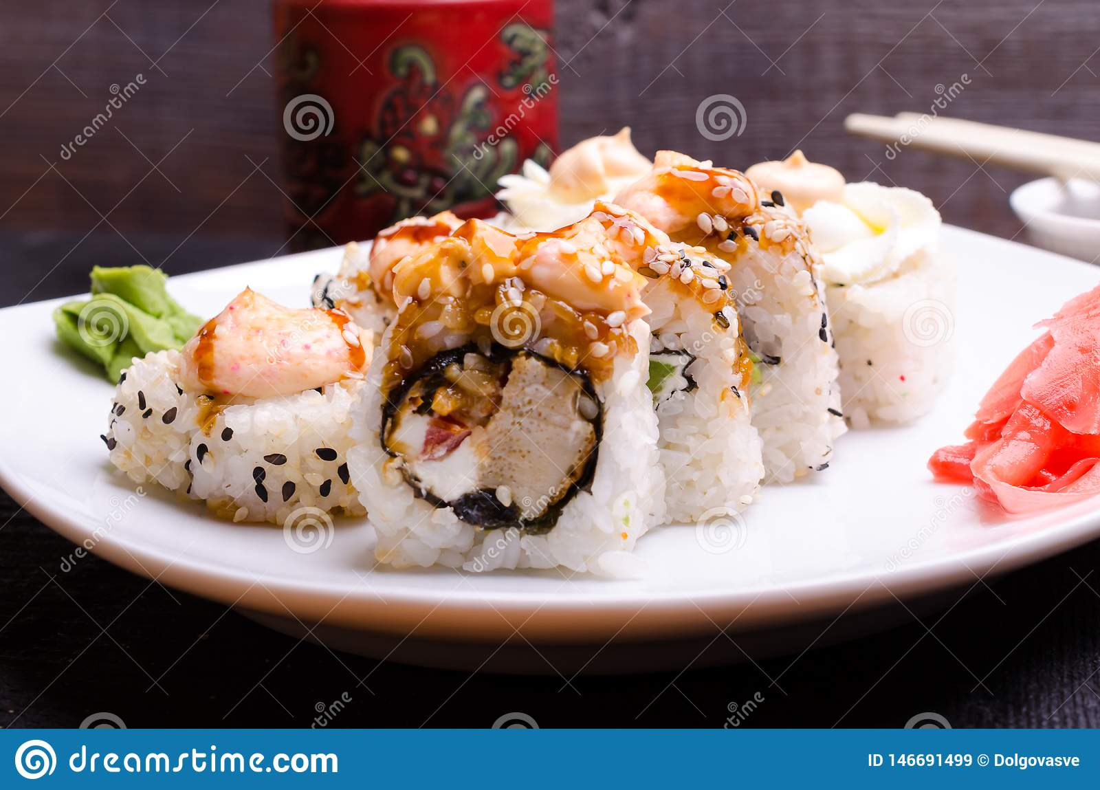 Sushi rolls on a white platter with ginger