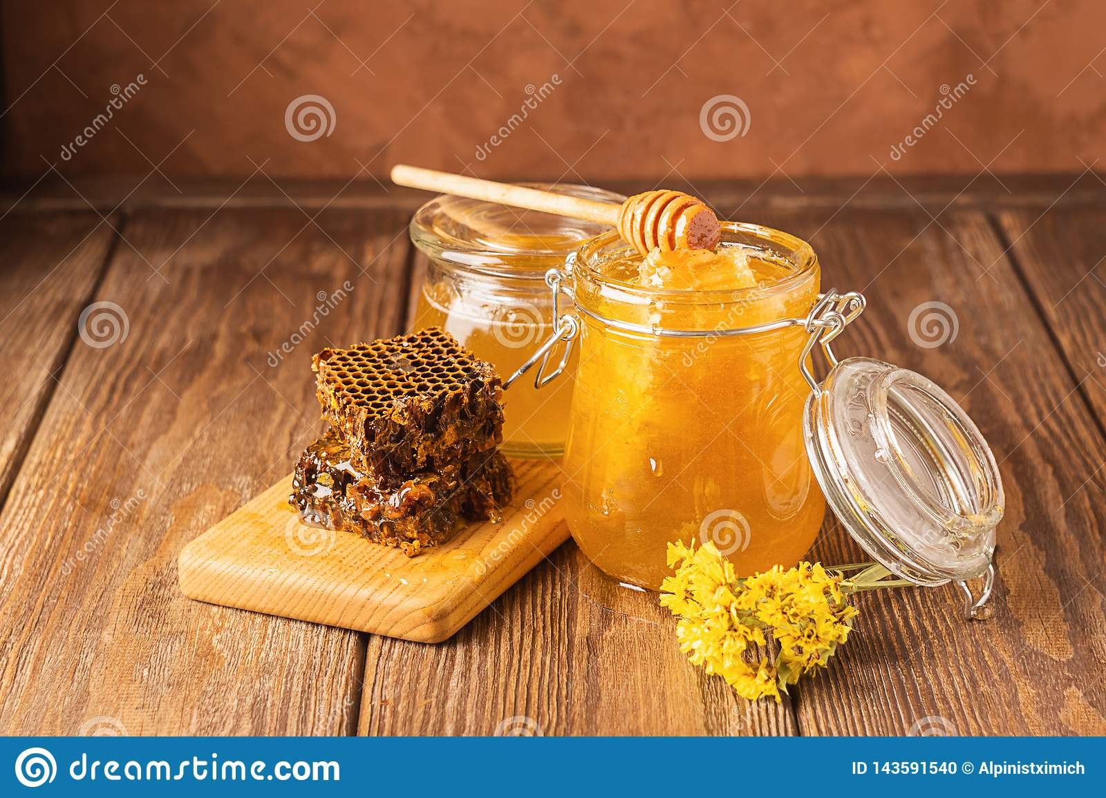 Fresh fragrant honey in a glass jar on a wooden background on the table. Different types of bee honey. Natural products.
