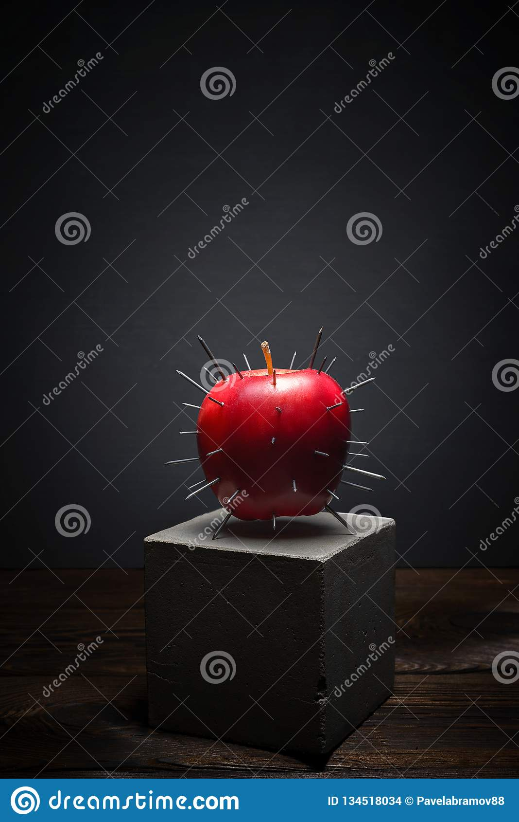 Fresh fruit on dark background on concrete stand. Juicy red Apple with sharp thorns