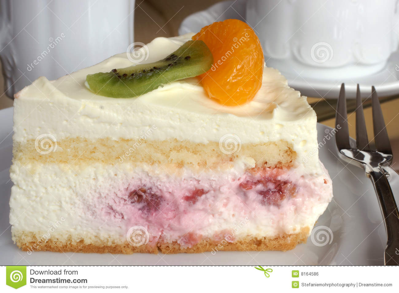 Fresh fruit torte on a plate with a silver cake fork cup and milk jug ...