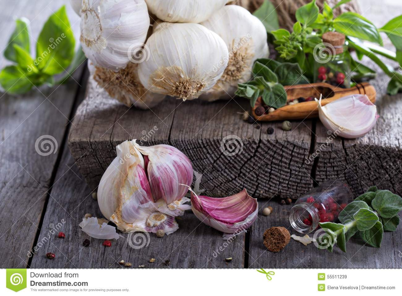 Fresh garlic, spices and salad leaves on table