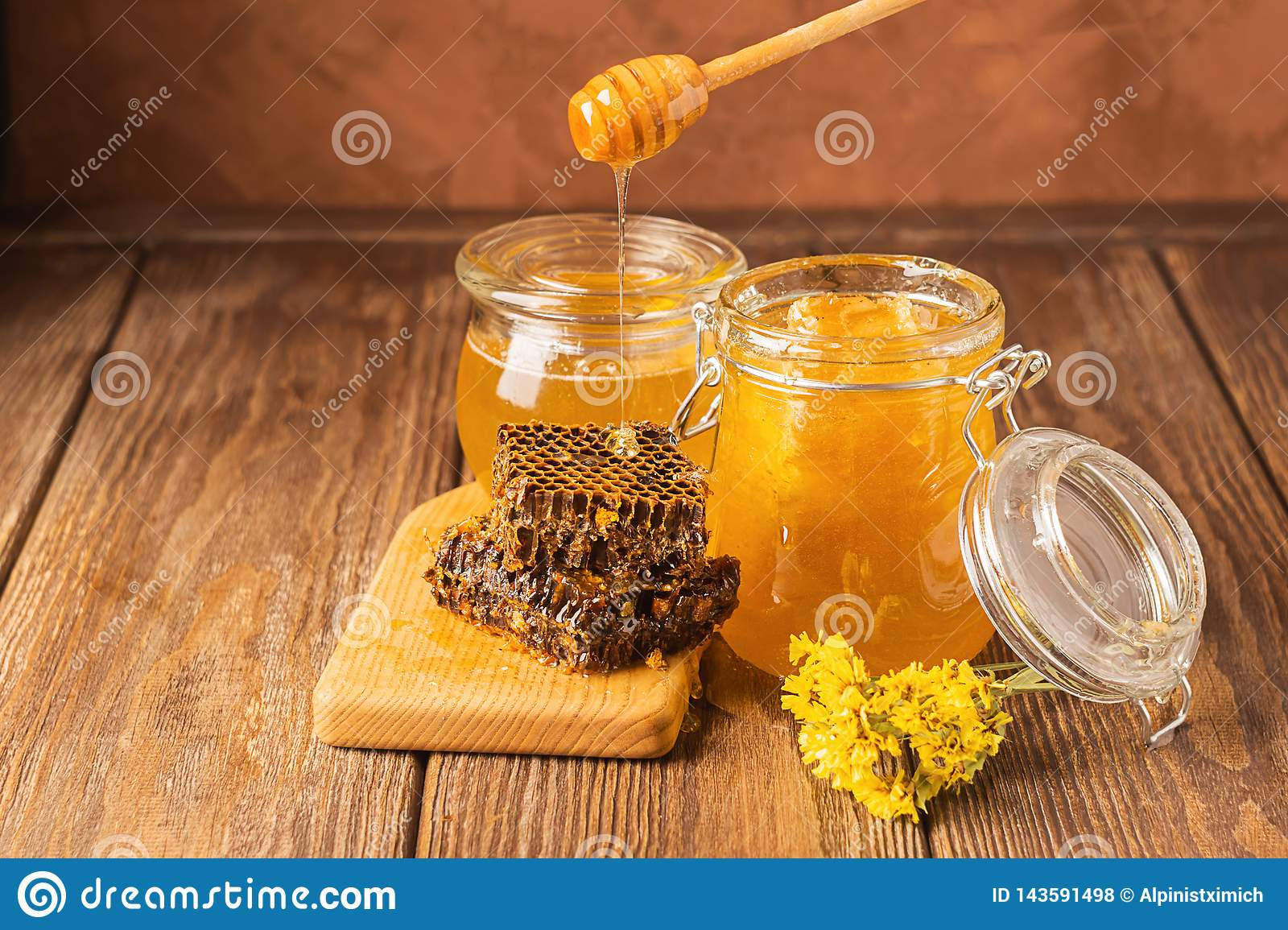 Fresh golden honey flows from a wooden spoon into a jar. Bee aromatic honey on a wooden background on the table.