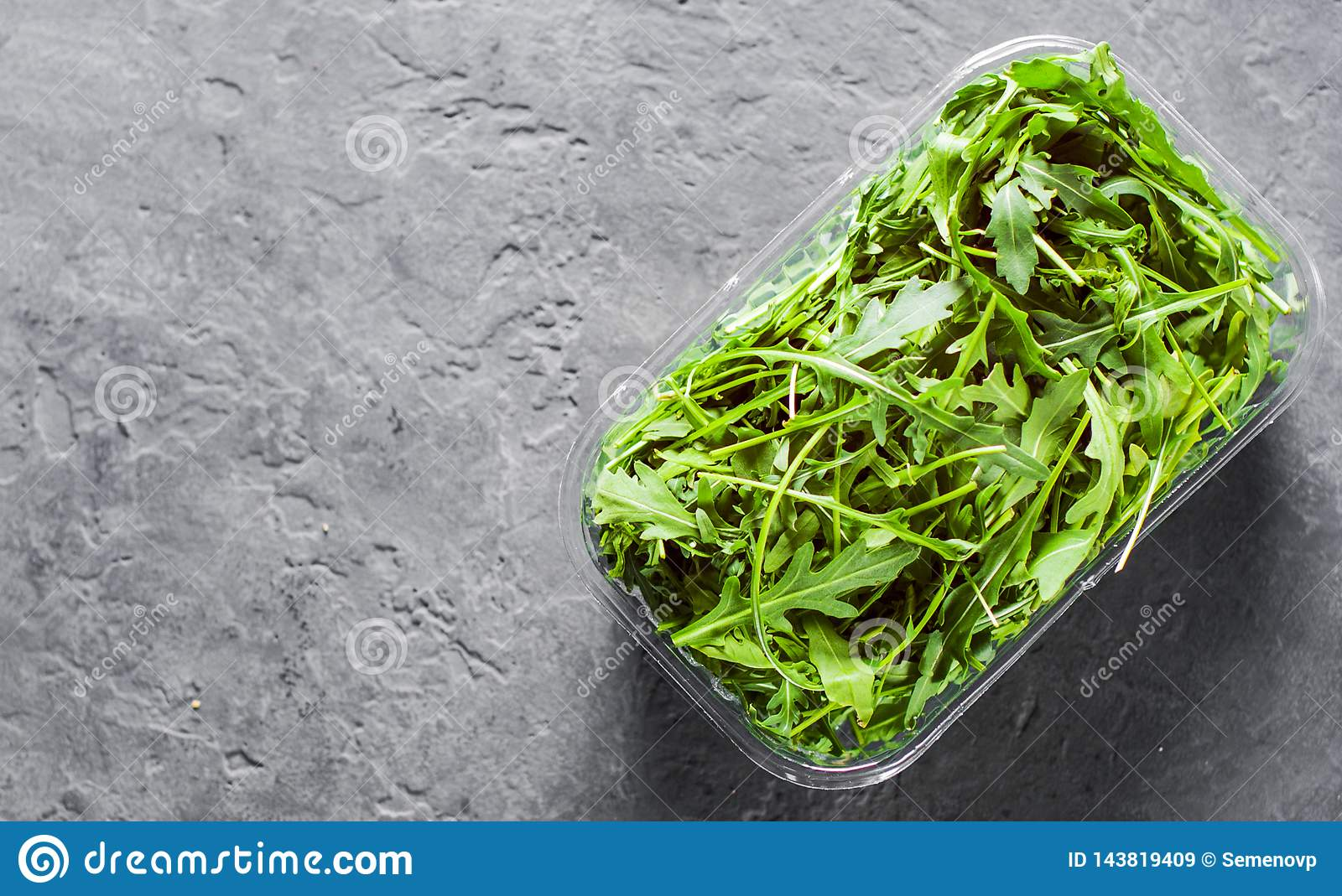 Fresh green arugula leaves in a plastic package box on Dark grey black slate background with copy space