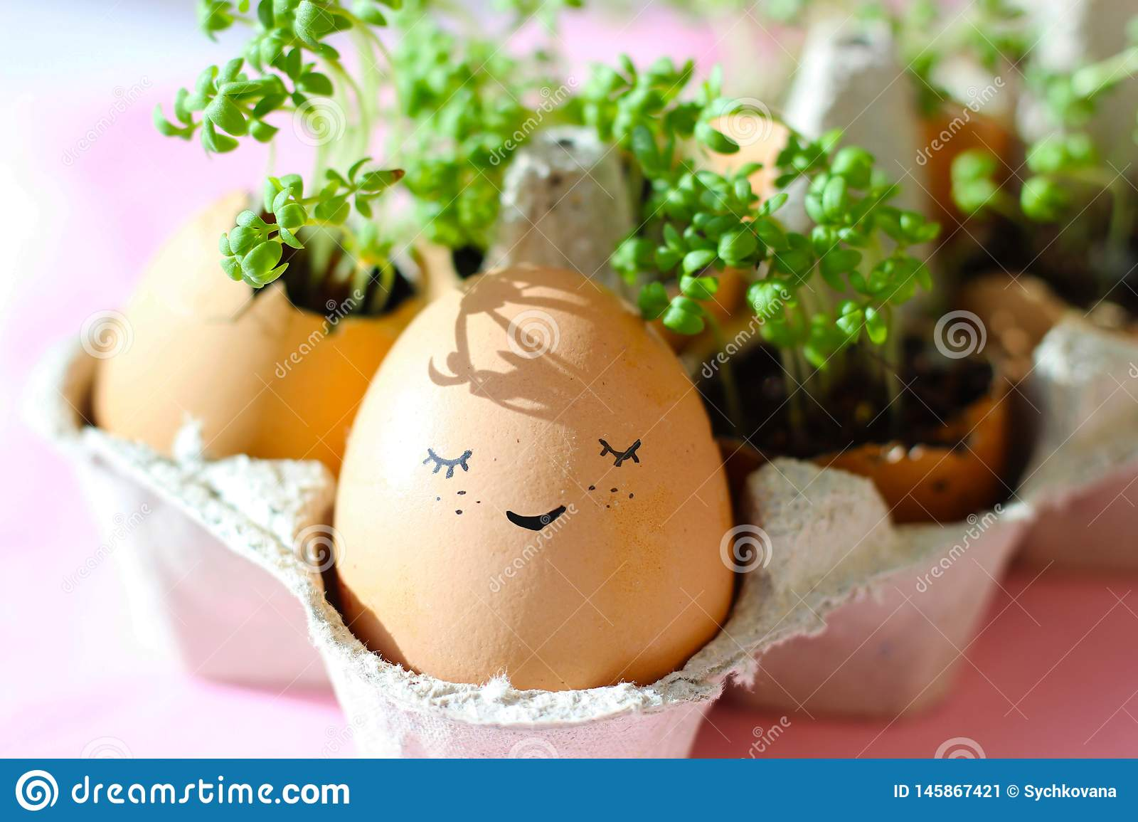 The fresh green grass growing in an egg shell with the funny persons drawn on it. The idea of spring creativity for